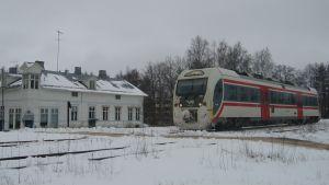 En rälsbuss vid en plankorsning i vintriga Hangö.