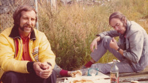 Arkivfoto från 1970-talet där två män äter medhavd matsäck ute i det fria.