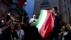Femstjärnerörelsens Luigi di Maio håller upp den italienska flaggan under ett möte med anhängare i Neapel.