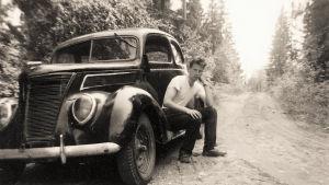 Svartvit bild av en ung man som sitter vid sin bil på en skogsväg.