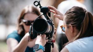 Kaksi Yle ulkotuotantojen naista virittävätä kameraa