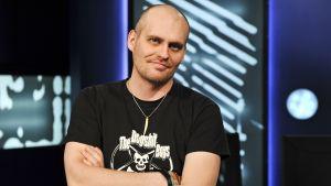 Lasse Grönroos i Yle Fem-programmet Tredje Statsmakten, i studion med händerna i kors.