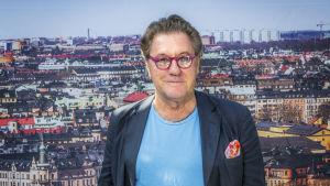 Tommy Körberg i färggranna glasögon och med Stockholm i bakgrunden.