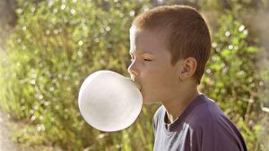 Poika puhaltaa purkkapalloa