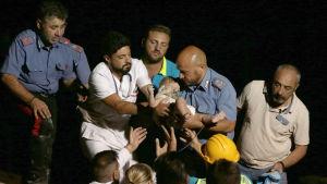 Räddningsarbetarna lyfter upp sju månader gamla Pasquale ur rasmassorna.