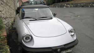 Hopeanharmaa, urheilumallinen Alfa Romeo pysäköitynä kadulle kivimuurin viereen.