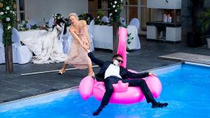 Man i kostym ligger avtuppad på en uppblåsbar flamingo i en pool. Han fru försöker dra upp honom.