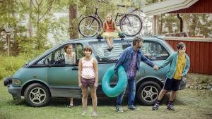 Perhe täyteen pakatun auton edessä. Yksi lapsi istuu katolla.