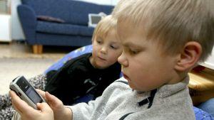 Två pojkar tittar på en mobiltelefon