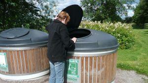 Kvinna kastar sopor i stort sopkärl