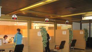 Klienter anmäler sig vid mottagningsdesk på Lojo sjukhus.