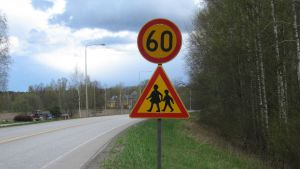 Hastighetsbegränsing 60 km/h samt trafikmärke som varnar för barn.