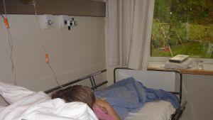 En ungdom som ligger i en sjukhussäng på barnavdelningen.