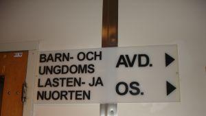 """En skytl med texten """"Barn- och ungdomsavdelning"""" på svenska och finska."""