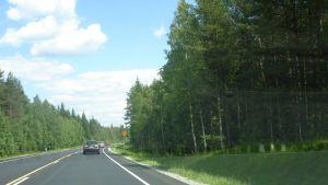 Bil kör förbi trafikmärke som visar högsta tillåtna hastighet.