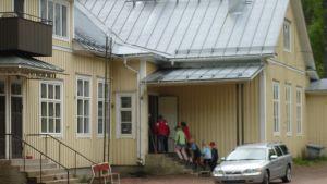 Elever går uppför trappan in i träskola.