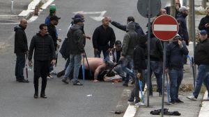 Skottskadad Napolisupporter tas om hand på gatan i Rom.