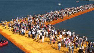 Folk går på vatten på Christos konstverk Flytande pirer.