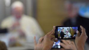 Påven fotograferas med mobiltelefon.