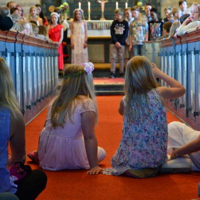 Några flickor sitter i altargången i en kyrka. Uppe vid altaret står uppklädda skolelever.
