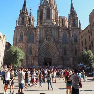 Turister utanför en katedral i Barcelona.