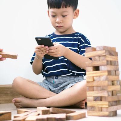 En pojke som tittar ner i sin mobiltelefon.