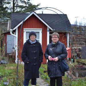 Marga Brunila och Kristina Virtanen från Brunakärr koloniträdgårdsförening står framför Brunilas kolonistuga.