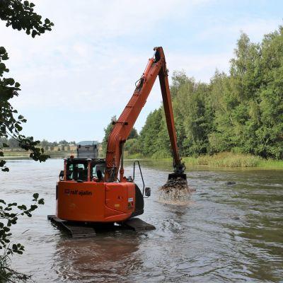 En grävmaskin arbetar i en å.
