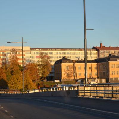 Räcket på Vasklotbron syns. I bakgrunden syns en stor gul byggnad och några höghus.
