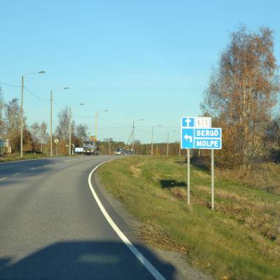 Två bilar kör på Strandvägen i Korsnäs. Blå skylt som visar pil till vänster mot Bergö och Molpe.
