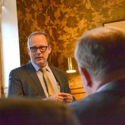 Tomas Häyry står framför människor och pratar.