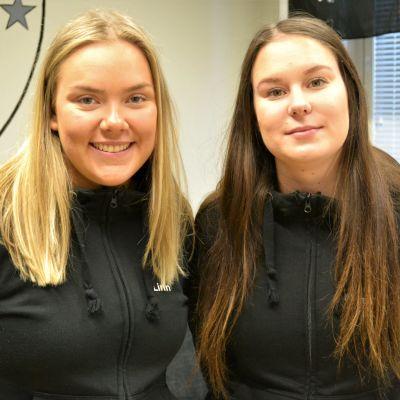 Två flickor med svarta munkjackor står bredvid varandra.