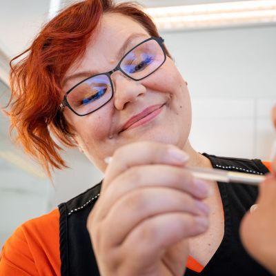 Toimitusjohtaja Riina Sorjonen meikkaa asiakasta.