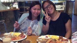 Två kinesiska kvinnor på en restaurang. På tallrikarna har de en traditionell english breakfast.
