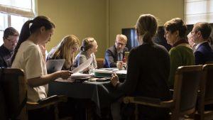 En grupp människor har samlats kring ett bord för regeringsförhandlingar i Ständerhuset.