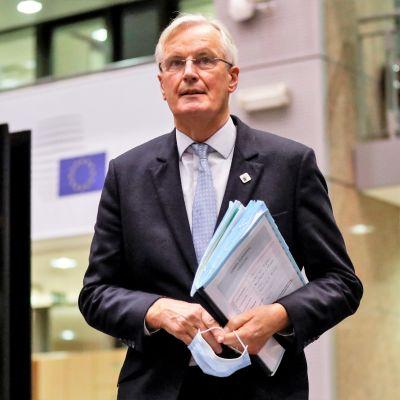 Michel Barnier kulkee kansion ja kasvomaskin kanssa isossa salissa. Seinällä näkyy EU-lippu.