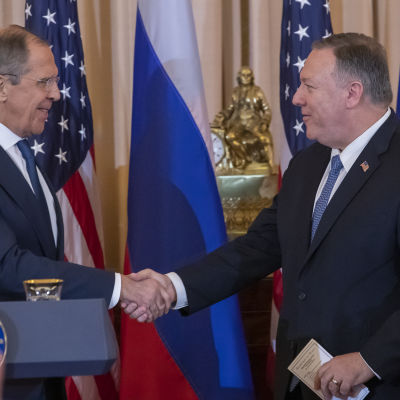 Två män i kostym skakar hand med flaggor i bakgrunden.