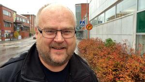 En man står ute på gatan i regnet. Det är höst. Mannen heter Ben Wiberg och han står utanför Fokus-huset i Karis.