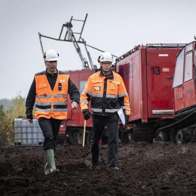 Hannu Hautala ja Pentti Grönholm kävelevät turvesuon reunalla. Taustalla kairauskone.