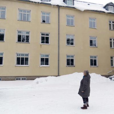 En kvinna står i ett vintrigt landskap och tittar på en stor byggnad.