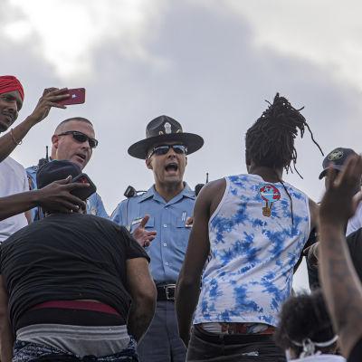 En samling människor. I mitten står en polis och pratar med en mörkhyad man.
