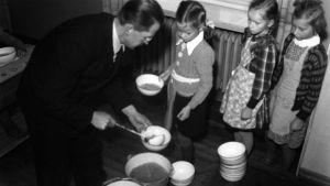 Svartvit bild av barn som får skolmat 1943.