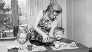 En mamma häller upp mjölk åt sina barn vid matbordet.