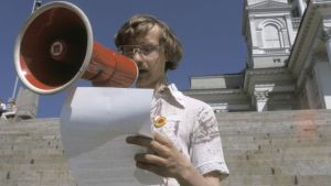 Nuori mies puhuu megafoniin paperi kädessä.