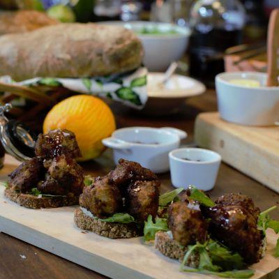 Portioner med kalkonköttbullar på brödskivor med cumberlandsås på en skärbräda