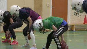 Ungdomar iklädda dräkter för amerikansk fotboll övar dribbla på rad med en oval boll.
