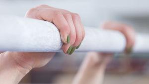 Två händer som håller i ett gymnastikredskap.