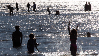 Ungdomar som simmar och vada i vatten. Det är i Helsingfors, Sandudds badstrand.