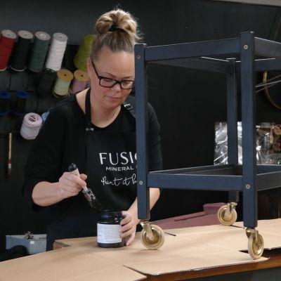 Minna Lindberg målar ett bord svart vid butiksdisken