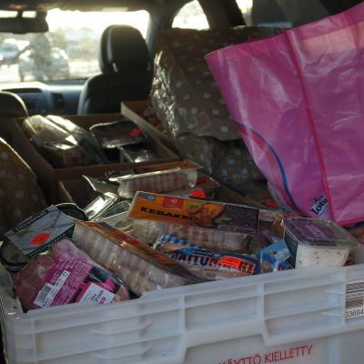 Överbliven mat som går till matutdelning har packats ihop i en bil